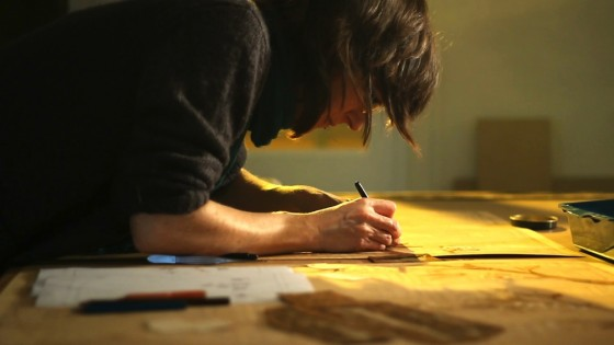 Anne lays sand-shaded veneer pieces into a panel