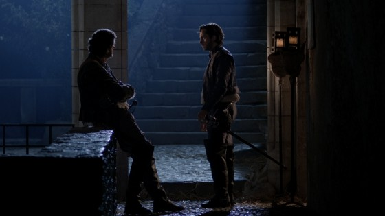 This night exterior shot of Lazare (Tony Sams) and Athos (Edward Mitchell) was shot with a white balance of 3,200K, turning the HMI backlight blue, while the warm light around the taven entrance was provided by CTO-gelled Dedos and redheads.