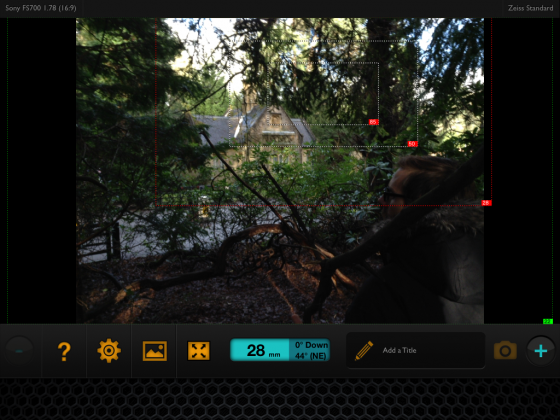 The cottage exterior seen from amongst the trees opposite, through the Artemis director's viewfinder app