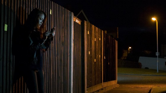 The orange backlight on Faith (Haruka Abe) and the fence, although apparently from the streetlamp in the background, is actually from an Arrilite 650 out of frame right, gelled with Urban Sodium. A daylight-balanced LED panel, also out of frame right but closer to camera, keys Faith. A second panel hidden behind the end of the fence lights the van and the rest of the deep background.